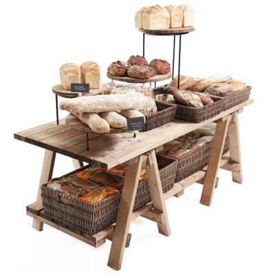 Low-Trestle-table-with-merchandiser-risers-and-wicker-for-bakery-display